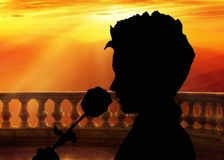 Walentynka dnia tło, sylwetka trzyma róży i wącha je, stojący na balkonie przy zmierzchem, romantyczna sceneria fotografia stock
