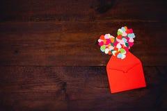 Walentynka dnia twórczość, DIY prezent, karciani pomysły Wiele stubarwni papierowi serca z czerwienią tapetują kopertę na drewnia fotografia stock