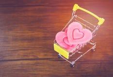 Walentynka dnia zakupy menchii serce na wózek na zakupy miłości Robi zakupy wakacje dla miłość walentynek dnia na drewnianym obraz stock
