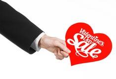 Walentynka dzień i sprzedaż temat: Ręka mężczyzna trzyma kartę w postaci czerwonego serca z słowo sprzedażą w czarnym kostiumu Fotografia Royalty Free