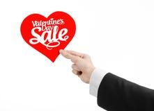 Walentynka dzień i sprzedaż temat: Ręka mężczyzna trzyma kartę w postaci czerwonego serca z słowo sprzedażą w czarnym kostiumu Obrazy Royalty Free