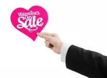 Walentynka dzień i sprzedaż temat: Ręka mężczyzna trzyma kartę w postaci różowego serca z słowo sprzedażą w czarnym kostiumu Fotografia Stock