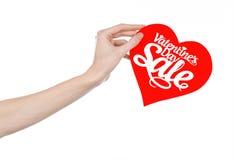 Walentynka dzień i sprzedaż temat: Wręcza trzymać kartę w postaci czerwonego serca z słowo sprzedażą odizolowywającą na białym tl Obrazy Royalty Free