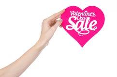 Walentynka dzień i sprzedaż temat: Wręcza trzymać kartę w postaci różowego serca z słowo sprzedażą odizolowywającą na białym tle Zdjęcia Royalty Free