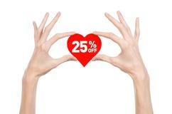 Walentynka dzień pomija temat: Wręcza trzymać kartę w postaci czerwonego serca z rabatem 25% na odosobnionym Fotografia Stock