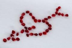 Walentynka kierowy kształt z strzałą robić granatowów ziarnami na białym śniegu zdjęcia royalty free