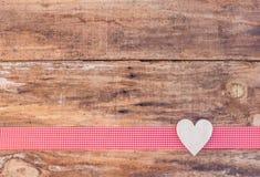 Walentynki kierowa dekoracja na czerwonym faborku rabatowym i nieociosanym drewnianym tle Fotografia Royalty Free