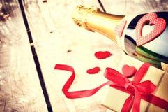 Walentynki położenie z teraźniejszością i butelką szampan Obrazy Stock