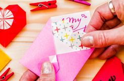 Walentynki ` s dnia wakacje kobiety ` s ręka z origami sercem stawiać papierowego serce różowa koperta fotografia stock