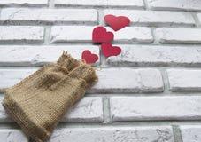 Walentynki ` s dzień, czerwonych serc brezentowa torba, tło bielu ściana z cegieł Obraz Royalty Free