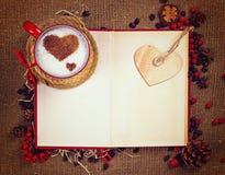 Walentynki ` s pocztówka Filiżanka kawy na otwartej książce z drewnianym sercem na nim Obraz Royalty Free
