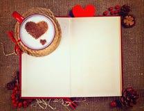 Walentynki ` s pocztówka Filiżanka kawy na otwartej książce z drewnianym sercem na nim Zdjęcie Stock
