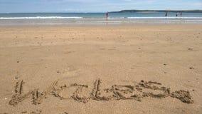 Wales som är skriftlig i sanden på stranden i Tenby, Wales Royaltyfri Bild