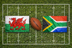 Wales vs. South Africa flags on rugby field. Wales vs. South Africa flags on green rugby field Stock Image