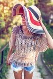 waling在公园的帽子的妇女在夏天 免版税库存照片