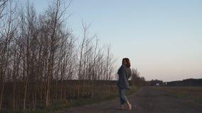waling在领域的年轻女人在金黄小时日落期间在与清楚的天空蔚蓝的晚上在背景中- 股票视频