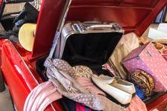 Walizka i pudełko z akcesorium jak but, kapelusz, płótno, torba i szalik w Pełnym bagażniku Czerwony samochód kobiet, Zdjęcia Stock