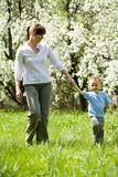 Walk. Lovely woman and her son in casual clothes taking a walk down green grass in summer Stock Photos