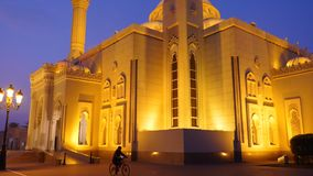 Walk along the Arabian mosque at night. A lone cyclist rides through the park alley. Illuminated gold lights mosque. Morning outdoors shot stock footage