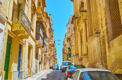 The ascent in St Ursula street, Valletta, Malta. Walk along the ascent in St Ursula street with a view on historical housing and colored Maltese balconies Royalty Free Stock Photography