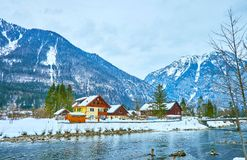 Wooden houses on bank of Traun river, Obertraun, Salzkammergut, Austria. Walk along the bank of Traun river with a view on mountains of Dachstein massif and stock photos