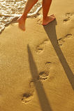 Walk along the beach, footprints in the golden sand Stock Photo