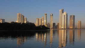Walk along Khalid lake in Sharjah city UAE. Al Noor island with trees at horizon. Skyline with skyscrapers at morning. Sunrise are shine. Outdoors stock video