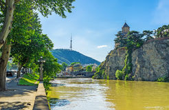 The walk along the Kura bank in Tbilisi. The shady Vakhtang Gorgasali embankment of Kura River is the perfect place for lazy walk, enjoying the cityscape Stock Image