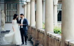 Walk along the old balcony of the stylish newlyweds holding hands and actively walking. Full-length portrait. Walk along the old balcony of the stylish Stock Photo