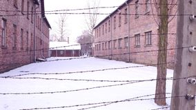Walk along old barbed wire fence of Auschwitz Birkenau concentration and extermination camp. Brick barracks in winter. 4K clip stock video footage