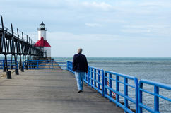 Walk along the pier. A silver haired man walks along the pier at the st Joseph north light pier and lighthouse in Michigan USA royalty free stock photos