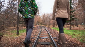 Walk Along The Rails. Man and Woman Walking in the Autumn Park stock video footage