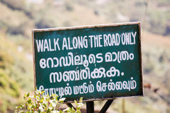 Walk along the road only. A sign tells people to stay on the road in English, Tamil, and Malayam Royalty Free Stock Photography