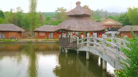 The pond in Santichon Chinese Yunnan cultural village, Thailand. Walk along the scenic pond with wooden bridge and watch traditional houses of Santichon Chinese stock video footage
