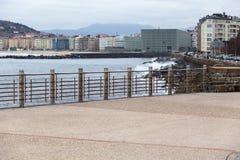 Promenade with metallic handrail. Walk along the sea with metallic handrail with sea and city royalty free stock photography