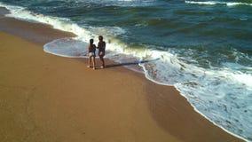 Walk along the seashore. Mom and daughter walk through the waves along the seashore stock video footage