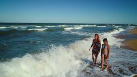 Walk along the seashore. Mom and daughter walk through the waves along the seashore stock video