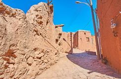 Street of Abyaneh, Iran. Walk along the steep ascent street with a view on preserved medieval houses walls of stones, erthern bricks and local reddish clay royalty free stock photos