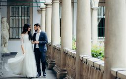 Free Walk Along The Old Balcony Of The Stylish Newlyweds Holding Hands And Actively Walking. Full-length Portrait. Stock Photo - 109982180