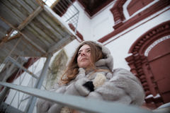 Walk around the city: the girl`s portrait in a gray short fur coat who stands behind handrail and looks in distance. Walk around the city: the girl`s portrait in stock photos