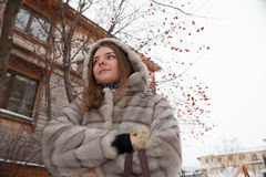 Walk around the city: the girl`s portrait at small lodge in the winter in a gray short fur coat Royalty Free Stock Photos
