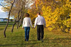 Walk through Autumn. A man and woman stroll through a park in autumn royalty free stock photos