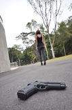 Walk Away. A lady walking away from a gun Royalty Free Stock Photos
