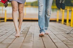 Bare male and female feet are on the footbridge of the lake pier. Walk barefoot in nature for two Royalty Free Stock Photography
