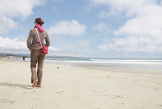 A walk on the beach. Fully dressed woman walking on a beach away from camera Stock Image