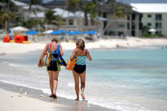 A walk on the beach. Two ladies walk on the beach as the talk stock photography