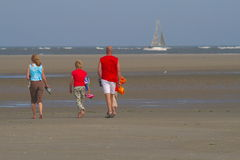 A walk on the beach. A back view of three adults, taking a relaxing walk on the beach with the wind blowing strongly Royalty Free Stock Photography