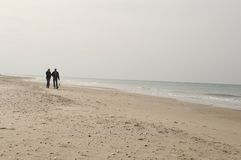 A Walk on the Beach. An adult male and female toddler walking on an empty beach Stock Images