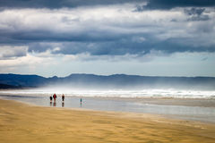 Walk on the beach. Family walking down 90 miles beach on a stormy day Stock Photo