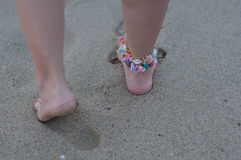 Walk on the beach. Female legs one bracelet ankle shells on the beach royalty free stock image